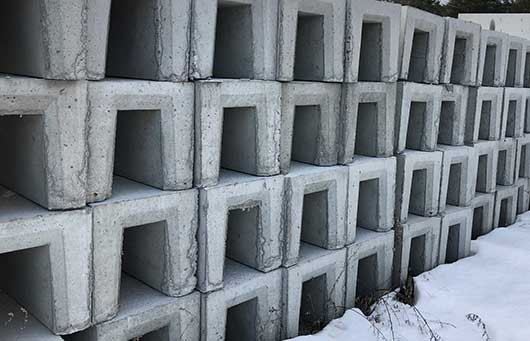 Photo of precast concrete trench drains stacked in supplier's yard.