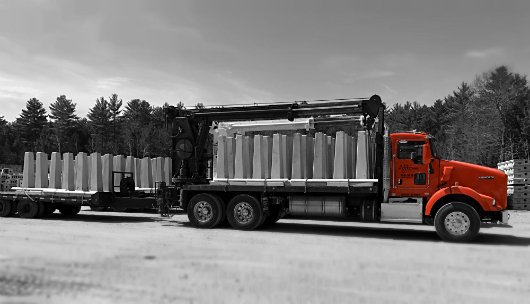 Photo of precast concrete frost posts on delivery truck.
