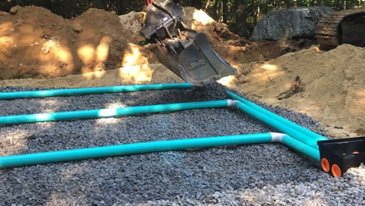 Pipe and stone leach field installation.